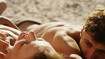 Young couple sunbathing on sunny beach - p1023m1156428 by Paul Bradbury