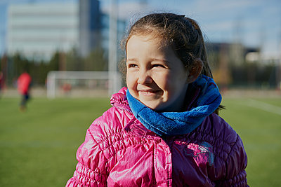 smiling little girl wearing a pink coat in a football stadium - p1166m2179596 by Cavan Images