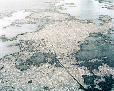 Map shaped puddles on sidewalk - p1409m1466048 by margaret dearing