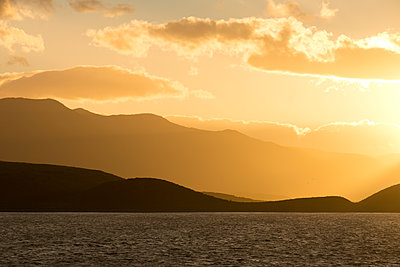 Golden sunset seen from the ocean shows the coastal mountains in silhouette; Ushuaia, Tierra de Fuego, Argentina - p442m2016249 by Philippe Widling