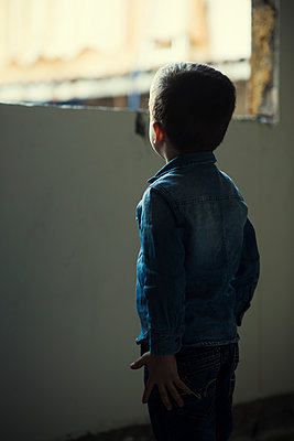 Rear view of a boy standing by the window  - p794m2031102 by Mohamad Itani