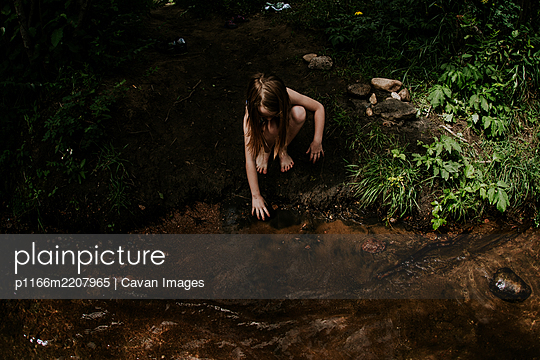 Overhead of young girl playing in the mud on the bank of a river - p1166m2207965 by Cavan Images