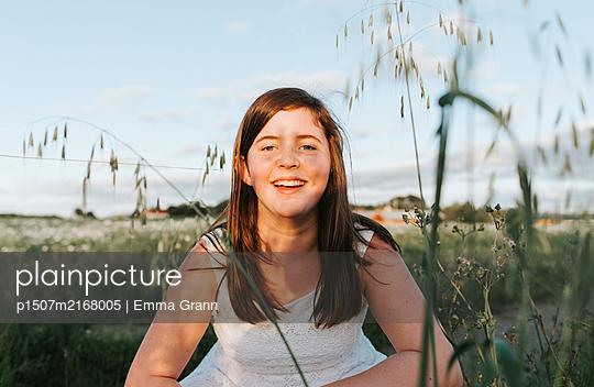 Girl in flower field - p1507m2168005 by Emma Grann