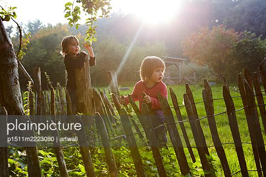 Zwei Kinder spielen im Garten - p1511m2223090 von artwall