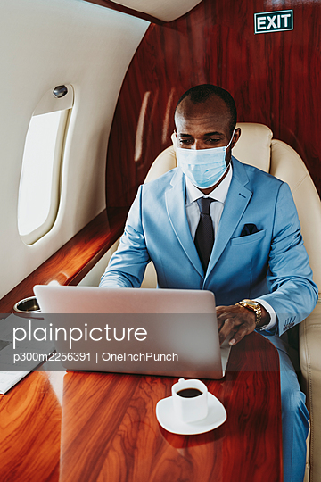 Male entrepreneur working on laptop in private jet during COVID-19 - p300m2256391 by OneInchPunch