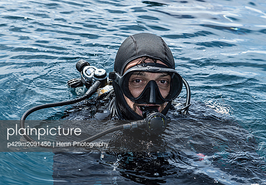 Male diver with head above sea water, portrait, Raja Ampat, Sorong, Nusa Tenggara Barat, Indonesia - p429m2091450 by Henn Photography