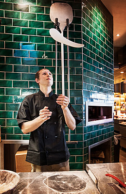 Male chef tossing pizza dough in commercial kitchen - p1166m1144688 by Cavan Images