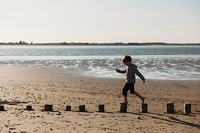 Side view of child balancing on log pilings on beach - p1166m2130801 by Cavan Images