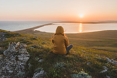 Woman in hooded jacket sitting on hill during sunset - p1427m2169351 by Oleksii Karamanov