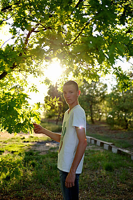 Youngster with short haircut under a tree - p1468m1584985 by Philippe Leroux