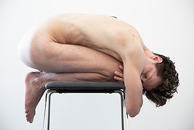 Naked young man on a chair - p1650m2272219 by Hanna Sachau