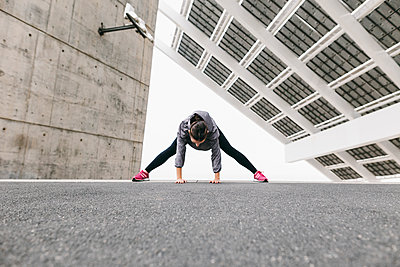Spain, Barcelona, female jogger, stretching excersice under solar plant - p300m1115190f by Bonninstudio