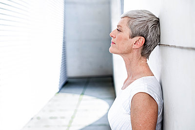Profile of pensive mature businesswoman leaning against wall - p300m2081366 by Viviane Wild