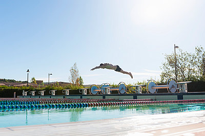 Mid adult man diving into swimming pool, Sardinia, Italy - p429m1006321f by Daniel Ingold