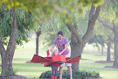 Father preparing toy airplane for his son in park - p429m943211f by Zero Creatives