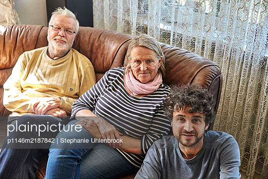 Family with adult son in the living room - p1146m2187842 by Stephanie Uhlenbrock
