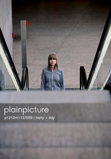 Junge Frau mit Kapuzenjacke vor Rolltreppe im Bahnhof - p1212m1137059 von harry + lidy