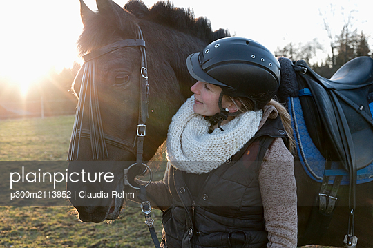 Smiling woman with horse at backlight - p300m2113952 by Claudia Rehm