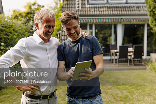 Happy son using digital tablet while standing by father in backyard - p300m2276951 by Gustafsson