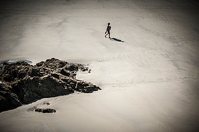 Single woman walking on beach - p1007m1216534 by Tilby Vattard
