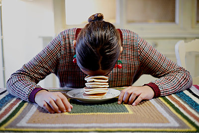 Young girl with face on a pile of pancakes - p1521m2128955 by Charlotte Zobel