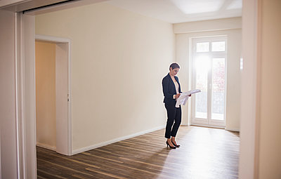 Woman in empty apartment looking at plan - p300m1459935 by Uwe Umstätter