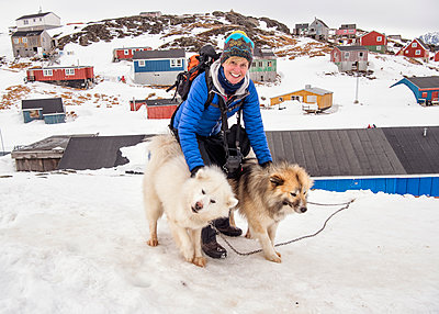 Greenland, Kulusuk, woman with Greenland huskies - p300m1588200 von Alun Richardson