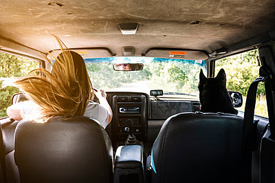 Blond woman with tousled hair by husky driving while on road trip - p300m2202713 by Jose Luis CARRASCOSA