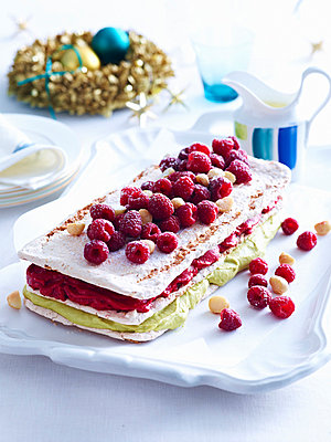 Tray of raspberry macadamia vacherin layer cake on decorated table - p429m872946 by BRETT STEVENS