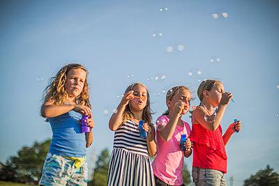 Girls blowing bubbles outdoors - p555m1411525 by John Fedele