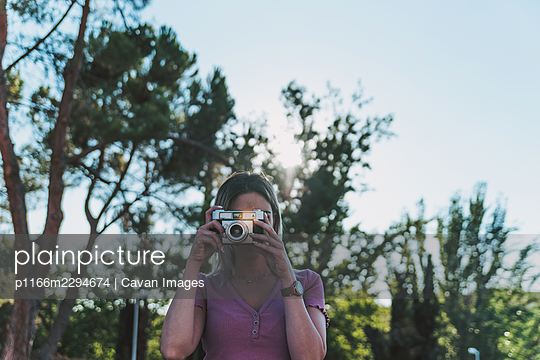 Blonde girl taking a picture with a retro camera. - p1166m2294674 by Cavan Images