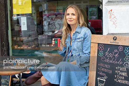Woman sitting at a bistro - p1678m2293087 by vey Fotoproduction