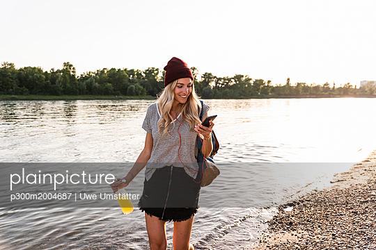 Young woman walking barefoot on riverside, earphones and smartphone - p300m2004687 von Uwe Umstätter