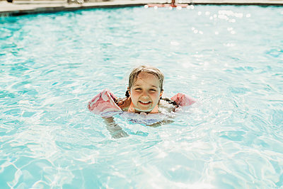 Young preschool age girl swimming in pool on vacation in Palm Springs - p1166m2218278 by Cavan Images