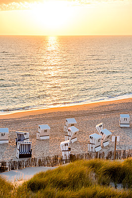 Germany, Schleswig-Holstein, Sylt, beach and empty hooded beach chairs at sunset - p300m1587421 by Ega Birk