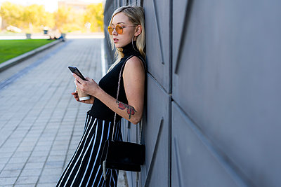 Fashionable young woman leaning against wall looking at smartphone - p300m2102982 by Giorgio Fochesato