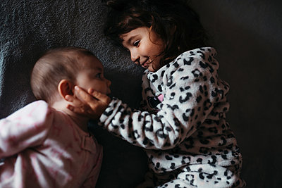 Girl touching baby sister's cheeks while lying on bed at hone - p300m2202636 by Gemma Ferrando