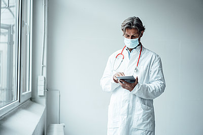 Mature male doctor using digital tablet in hospital during COVID-19 - p300m2293592 by Joseffson