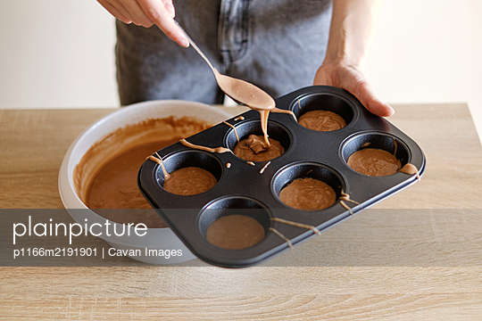 young woman pours chocolate dough into cupcake molds - p1166m2191901 by Cavan Images