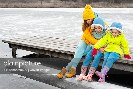 Mom with children sits on a wooden bridge by a frozen lake - p1166m2269620 by Cavan Images