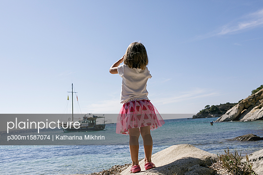 Back view of little girl with binoculars watching boat - p300m1587074 von Katharina Mikhrin