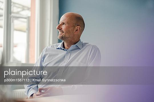 Smiling mature businessman looking out of window - p300m1587113 von Kniel Synnatzschke