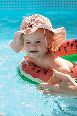 Little girl in a hat swims in the pool - p1166m2279431 by Cavan Images