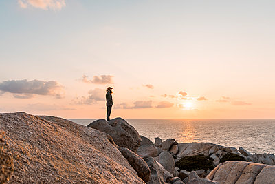 Italy, Sardinia, man standing on rock at sunset looking at view - p300m1580902 von VITTA GALLERY