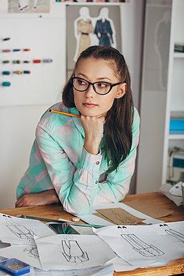 Thoughtful beautiful fashion designer looking away at workbench in studio - p301m1406573 by Vasily Pindyurin
