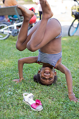 Happy girl doing headstand - p312m2262506 by Emma Sekhon