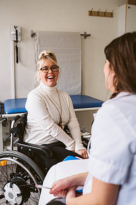 Cheerful disabled woman looking at female doctor in medical clinic - p426m2279752 by Maskot