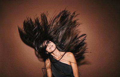 Junge Frau schüttelt ihre langen dunklen Haare - p586m953770 von Kniel Synnatzschke