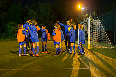 Girls soccer team listening to coach on field at night - p1023m2035189 by Paul Bradbury