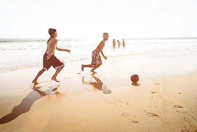 Side view of boys playing soccer on beach against clear sky - p1166m1098511f by Cavan Images